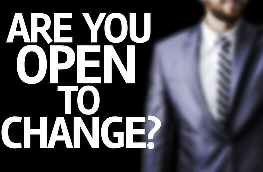 Are You Open to Change-written on a board with a business man on background
