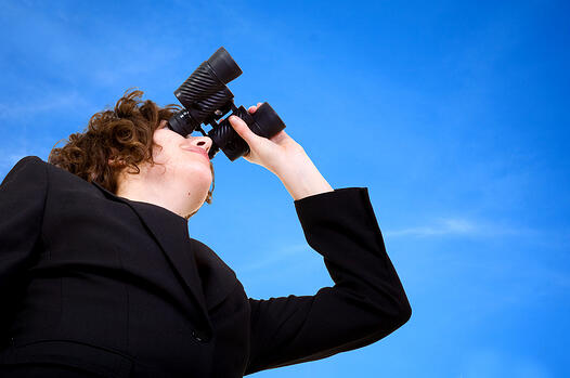 business vision - businesswoman looking through her binoculars over a blue sky