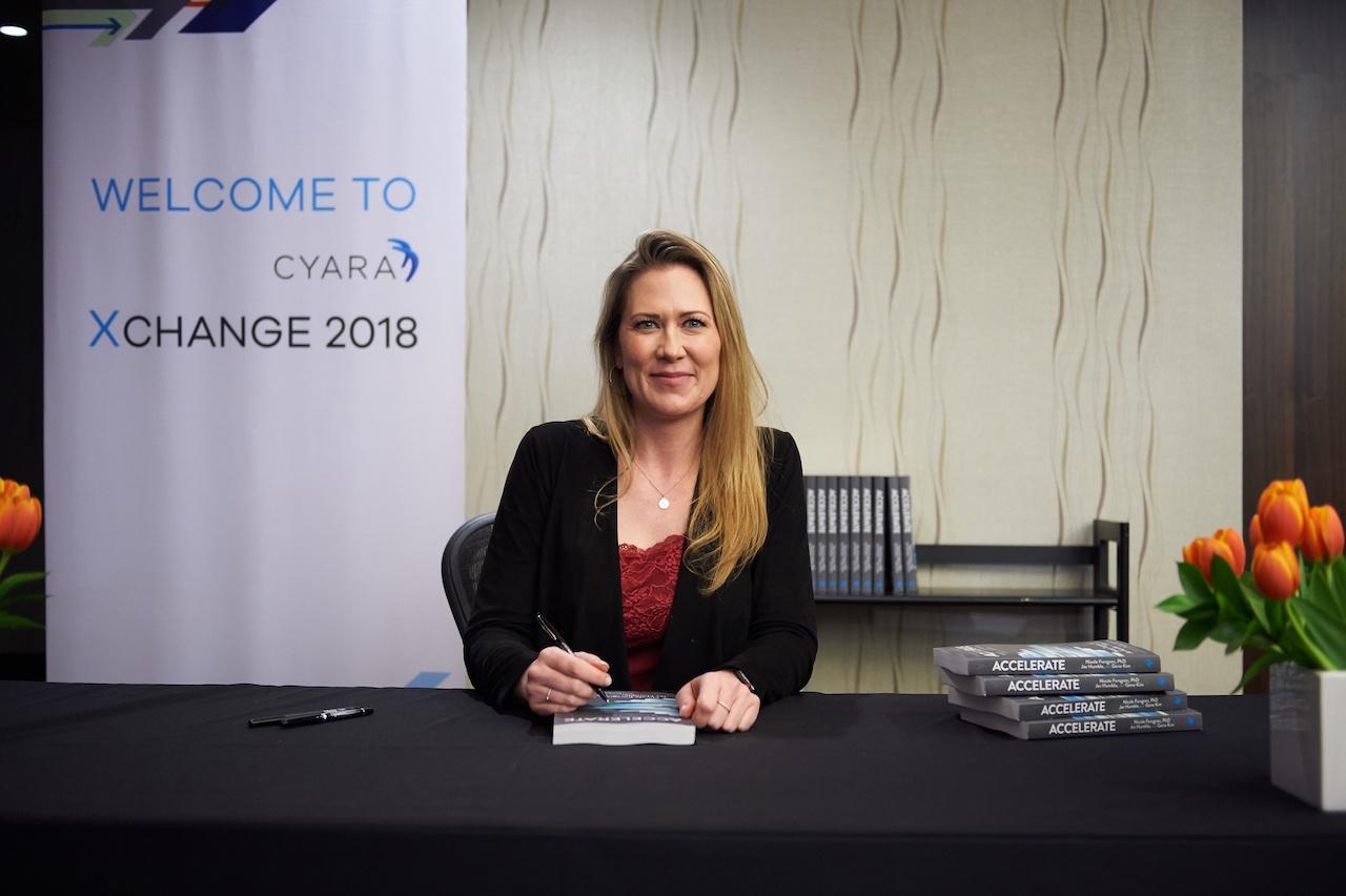 Dr. Nicole Forsgren signs copies of her new book at Cyara Xchange 2018